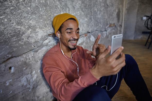 Indoor foto van gelukkig bebaarde donkere man met smartphone in opgeheven hand terwijl hij videogesprek voert, kijkt en glimlacht breed zittend op de vloer, in een hoge geest