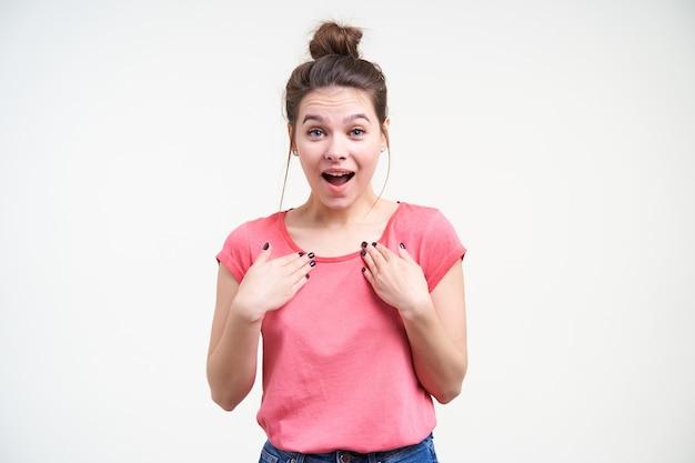 Indoor foto van jonge aantrekkelijke bruinharige dame raiaing verrast wenkbrauwen terwijl ze opgewonden naar de camera kijkt en handpalmen op haar borst houdt, geïsoleerd op witte achtergrond