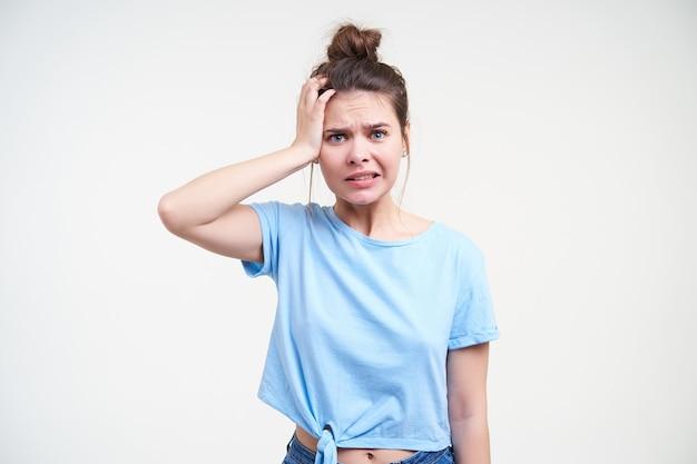 Indoor foto van jonge brunette dame gekleed in vrijetijdskleding met palm op haar hoofd en grimassen gezicht terwijl het kijken naar camera, geïsoleerd op witte achtergrond
