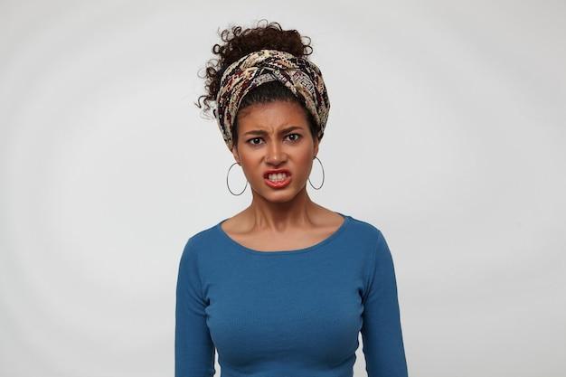 Indoor foto van jonge geïrriteerde donkerharige krullende dame met casual kapsel grimassen haar gezicht terwijl ze ontevreden naar de camera kijken, staande op witte achtergrond