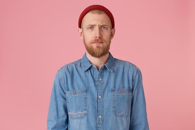 Indoor foto van jonge man in rode hoed met rode baard ziet er verdrietig, boos, vastgelopen man, ontevreden over iets, drukt droefheid melancholie uit, draagt modieus denim overhemd, geïsoleerd