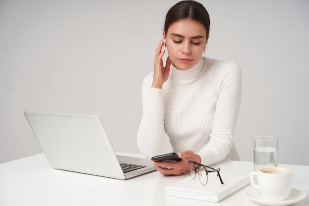 Indoor foto van jonge mooie brunette zakenvrouw hand opheffen naar haar oortje terwijl mobiele telefoon in de hand, zittend aan tafel over witte muur met moderne laptop