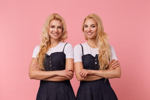 Indoor foto van jonge vrolijke langharige blonde vrouwtjes handen gekruist houden terwijl ze graag naar de camera kijken met een brede glimlach, staande op roze achtergrond