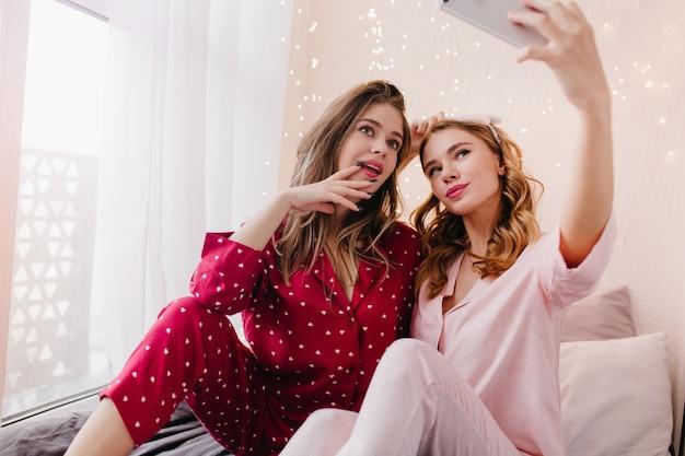 Indoor foto van lief blond meisje met behulp van telefoon voor selfie met vriendin. enthousiaste brunette dame in rood katoenen nachtkostuum poseren met zus.