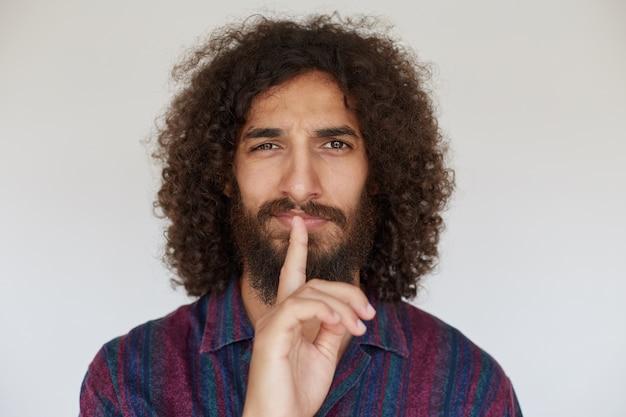 Indoor foto van mooie brunette bebaarde man in gestreept veelkleurig shirt hand opsteken in stil gebaar, wijsvinger op zijn lippen houden terwijl poseren