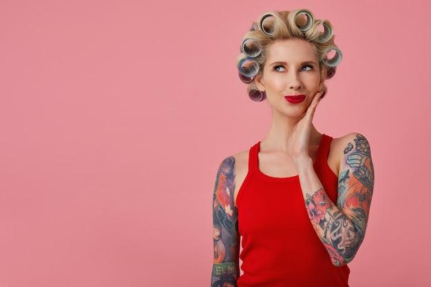 Indoor foto van mooie positieve jonge blonde dame met tattooes gekleed in een rood shirt dromerig op zoek naar boven met palm op haar wang, poseren op roze achtergrond met krulspelden op haar hoofd