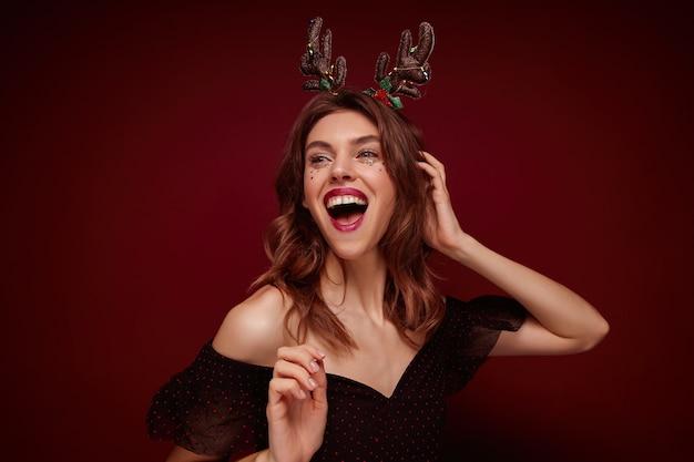 Indoor foto van mooie vrolijke jonge brunette dame met feestelijk kapsel chrismas hoorns en elegante kleding dragen terwijl poseren, ware positieve emoties uitdrukken