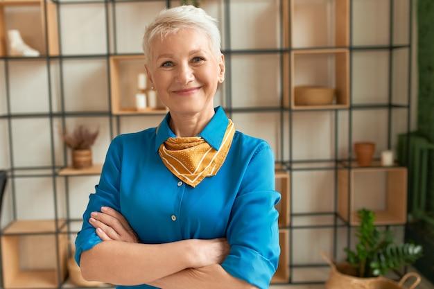 Indoor foto van optimistische energieke rijpe zakenvrouw met kort blond haar poseren in een stijlvol kantoor interieur met armen gevouwen op haar borst, camera kijken met zelfverzekerde gelukkige glimlach