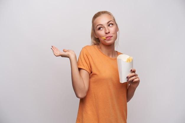 Indoor foto van positieve jonge mooie blonde vrouw in vrijetijdskleding schouderophalend met opgeheven handpalm en opzij kijken met vrolijke glimlach, met frietjes in haar mond