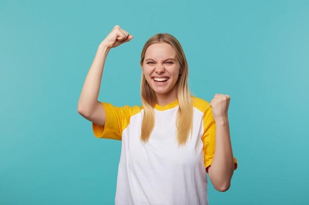 Indoor foto van vrolijke jonge blonde dame met casual kapsel vrolijk haar hand opheft en breed glimlachend, gekleed in een wit en geel t-shirt terwijl ze over een blauwe achtergrond staat