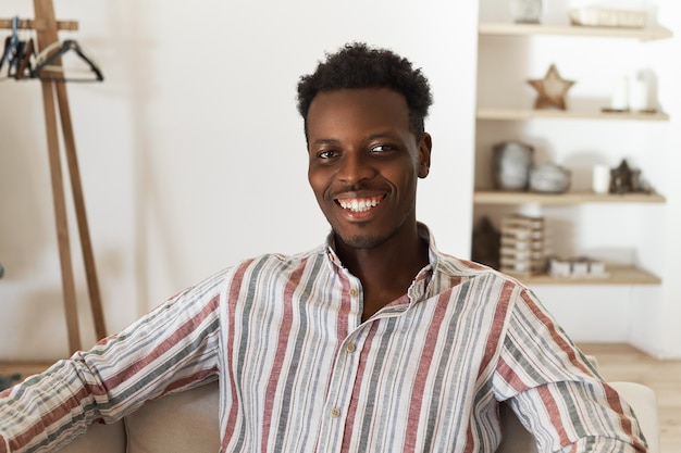Indoor foto van vrolijke positieve donkere jongeman met stijlvolle afro kapsel poseren tegen gezellige woonkamer interieur achtergrond camera kijken met gelukkige glimlach, ontspannen en zorgeloos gevoel