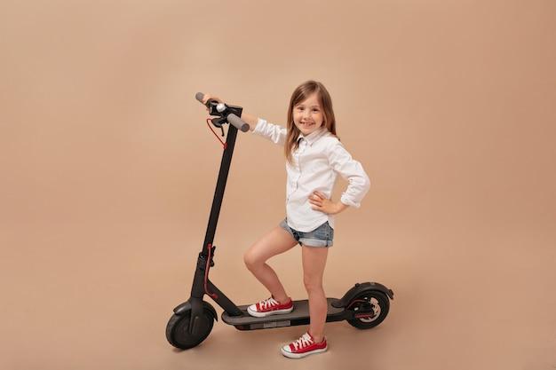 Indoor frame van klein schattig meisje poseren op camera over geïsoleerde beige achtergrond met elektrische scooter