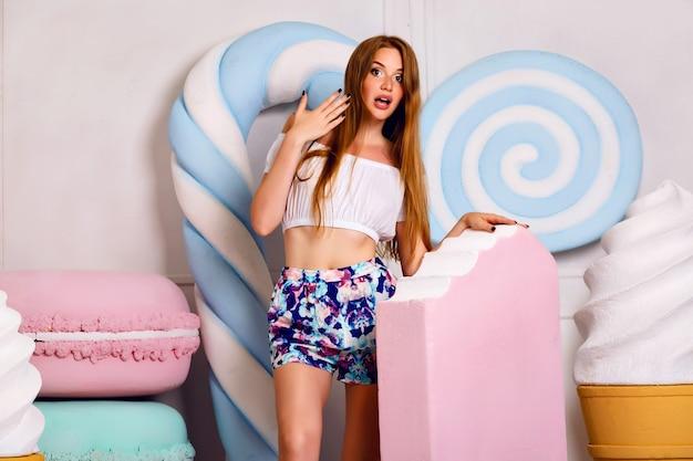 Indoor grappig beeld voor jonge blonde vrouw met gigantisch roze ijsje, verbaasde gekke emoties, lange haren natuurlijke make-up, grote zoetheid, franse bitterkoekjes en lollies.