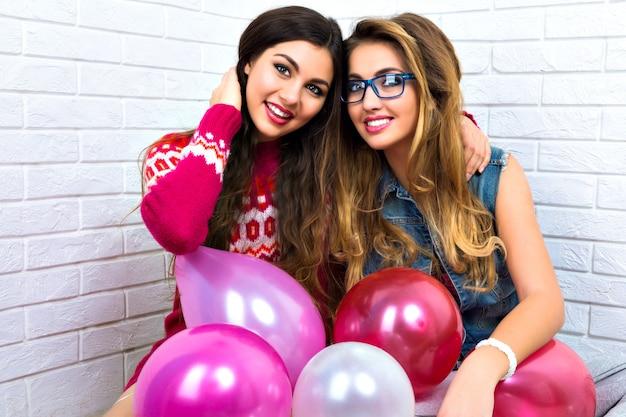 Indoor helder portret van twee grappige weddenschap vrienden zus hipster dames, gek, feest, roze ballon, knuffels en plezier, zussen, relaties, vakantie.