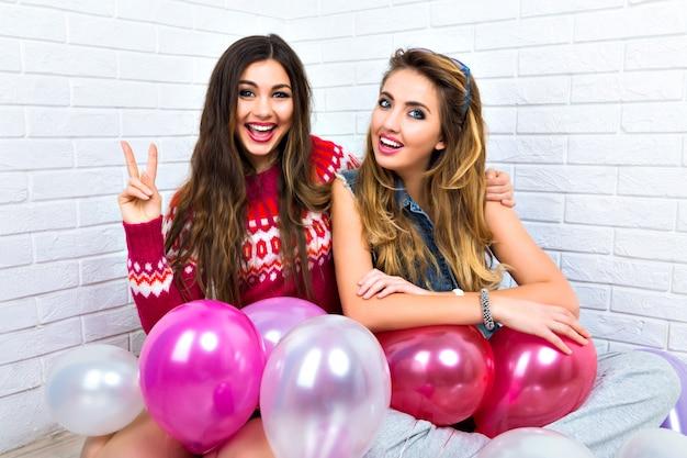 Indoor helder portret van twee grappige weddenschap vrienden zus hipster dames, gek, feest, roze ballon, v wetenschap, knuffels en kusjes, make-up, truien, geweldige glimlach tonen.