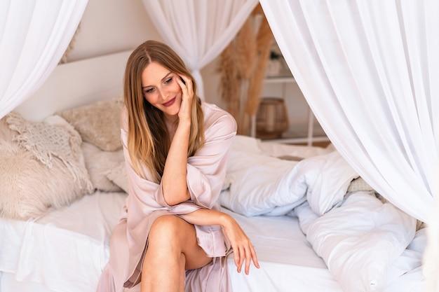 Indoor lifestyle mode portret van elegante blonde vrouw in beige zijden kimono ontspannen aan haar bed
