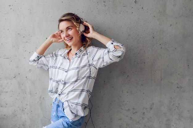 Indoor lifestyle portret van gelukkige enthousiaste vrouw luisteren naar muziek op stoel op grijze stedelijke muur achtergrond.