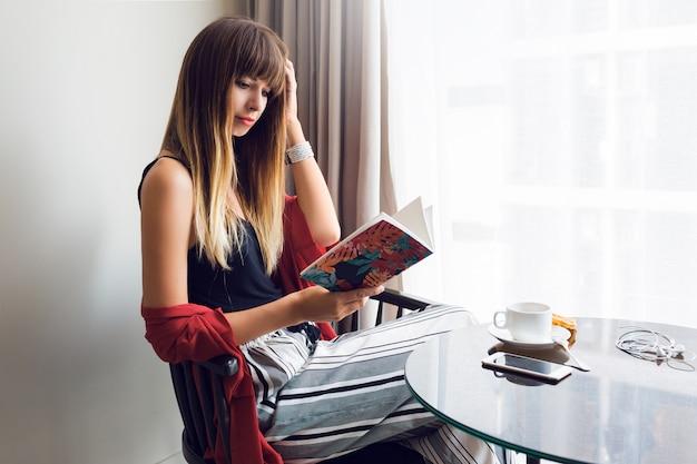 Indoor lifestyle portret van mooie brunette vrouw leesboek, zittend op een stoel en koffie drinken in zonnige lentemorgen. ontbijt tijd.