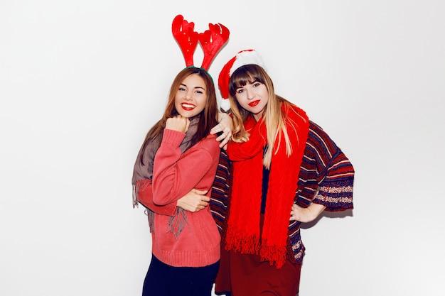 Indoor lifestyle portret van twee beste vrienden. vakantie make-up en leuke winter gezellige outfit, witte muur. maskeradehoeden dragen.