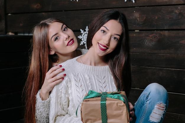 Indoor lifestyle portret van twee mooie jonge grappige vrouwen vrienden knuffels lachend