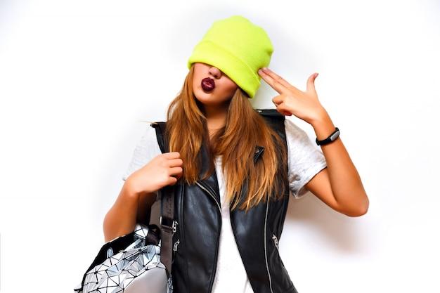 Indoor mode grunge portret van brutale hipster vrouw, leren jas, rockstijl, donkere lippen, flits, gekke emoties. zet een hoed op haar ogen, imiteer een pistool met haar hand, boos, slecht.
