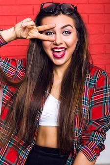 Indoor mode levensstijl portret van jonge mooie hipster vrouw met lichte make-up en geweldige glimlach, hebben lange donkerbruine haren, geruite overhemd dragen. rode stedelijke muur.