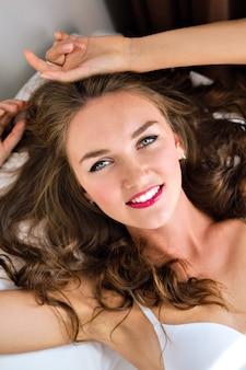 Indoor mode levensstijl portret van jonge verse geweldige vrouw die zich voordeed op het bed, verleidelijke lingerie dragen, ontspannen en plezier hebben in de ochtendtijd.