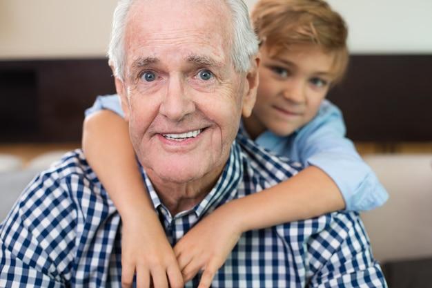 Indoor oude jongen grootouder omarmen
