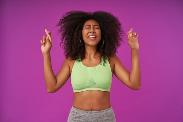Indoor portret van aantrekkelijke jonge donkere dame met krullend haar dragen lichtgroene top, handen opheffen met gekruiste vingers voor geluk, geïsoleerd op paars met gesloten ogen
