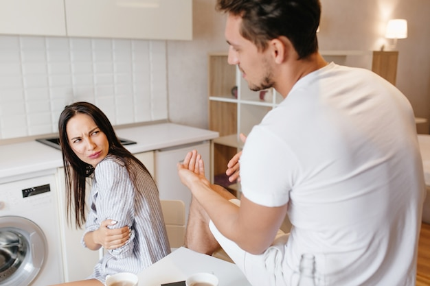 Indoor portret van achterkant brunette man praten met ongelukkige vrouw in mannelijke overhemd