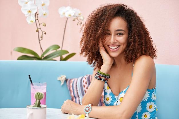 Indoor portret van afro-amerikaanse vrouw met borstelig krullend haar, zit aan tafel in cafetaria met cocktail, wordt in hoge geest, viert beginnende vakantie.