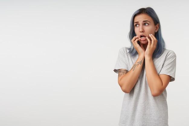 Indoor portret van bang jonge mooie getatoeëerde vrouw met kort kapsel met opgeheven handen op haar wangen en bang opzij kijken, geïsoleerd op wit