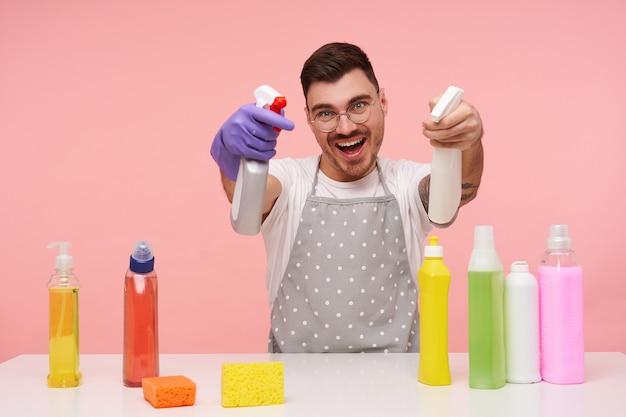 Indoor portret van blije jonge brunette man met kort kapsel gek terwijl het maken van de lente schoonmaak en glimlachen terwijl srpay flessen, geïsoleerd op roze