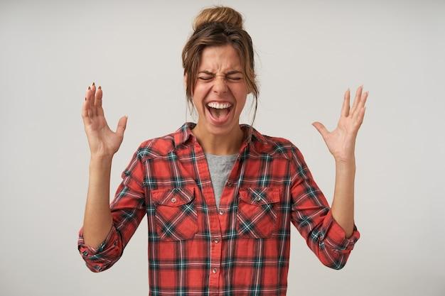 Indoor portret van boze jonge mooie vrouw permanent op wit met opgeheven handen, gewelddadig schreeuwen, geruit overhemd en broodje kapsel dragen