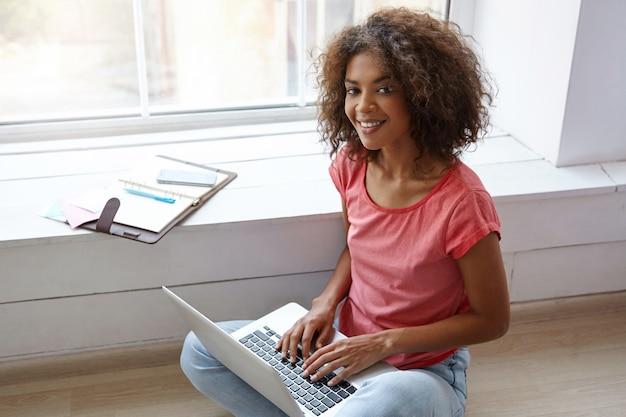 Indoor portret van charmante donkere vrouw met oprechte glimlach poseren over groot raam op zonnige dag, bezig met vensterbank met laptop en notebook