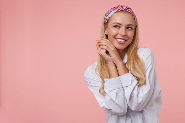 Indoor portret van charmante jonge vrouw met gevouwen handen in de buurt van haar gezicht, opzij kijken en breed glimlachen, vrijetijdskleding dragen, poseren