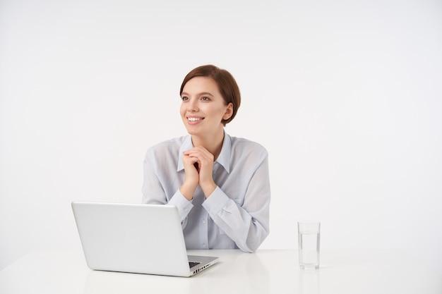 Indoor portret van charmante vrolijke jonge brunette vrouw met korte trendy kapsel, opgeheven handen vouwen en opzij kijken met een aangename glimlach, gekleed in formeel op wit