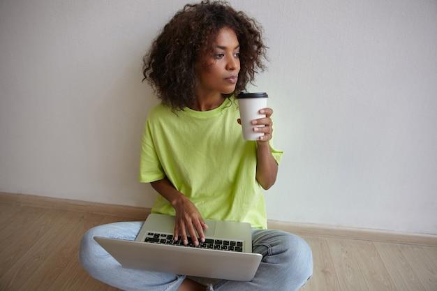Indoor portret van donkere huid jonge mooie vrouw met papieren beker in de hand, hand op toetsenbord houden en bedachtzaam opzij kijken, spijkerbroek en geel t-shirt dragen