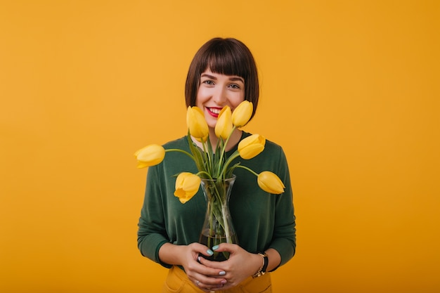 Indoor portret van donkerharige meisje in groene trui met vaas met mooie bloemen. extatische dame met kort haar staande met tulpen.