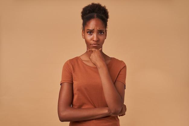 Indoor portret van doordachte jonge bruinogige donkere huid vrouw met opgeheven hand op haar kin en serieus kijken, poseren op beige