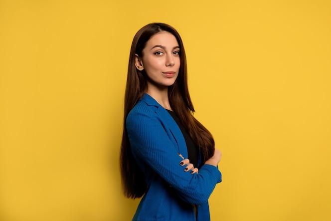 Indoor portret van een succesvolle jonge vrouw met lang donker haar gekleed in een blauwe jas poseren met gevouwen armen over gele muur