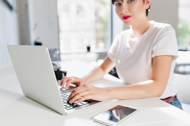 Indoor portret van elegante brunette vrouw in wit overhemd met moderne laptop en smartphone op voorgrond