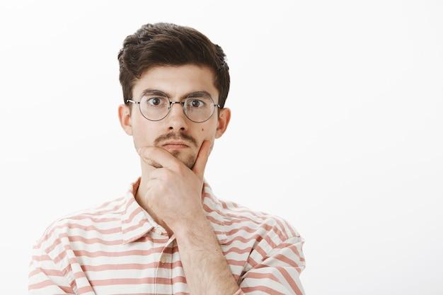 Indoor portret van ernstige gerichte mannelijke nerd in trendy ronde bril, kin wrijven met hand en staren, denken of een beslissing nemen, wiskundig probleem oplossen over grijze muur