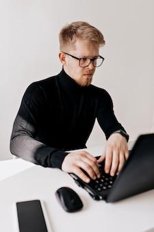 Indoor portret van europese jonge man met zwarte trui en bril werken met laptop in het lichte kantoor in zonnige dag.