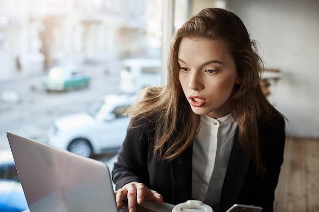 Indoor portret van gehinderde en verwarde stijlvolle vrouw zitten in cafe, werken met laptop, kijken scherm met verbaasde uitdrukking