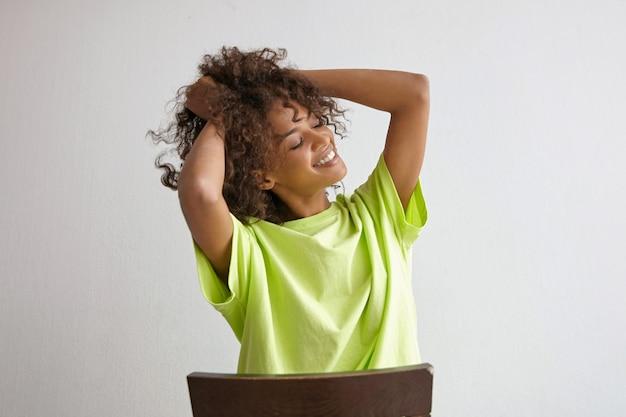 Indoor portret van gelukkig aantrekkelijk krullend vrouw met donkere huid, zittend op een stoel, haar haar met handen vasthoudend, vrolijk glimlachend met gesloten ogen