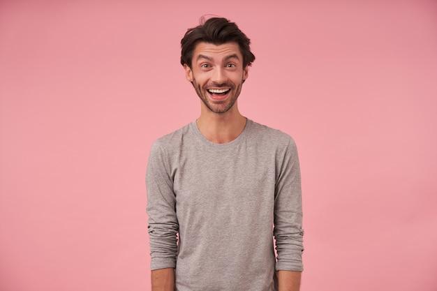 Indoor portret van gelukkig bebaarde man met trendy kapsel, het dragen van vrijetijdskleding, poseren met de handen naar beneden, vrolijk op zoek met brede mond geopend