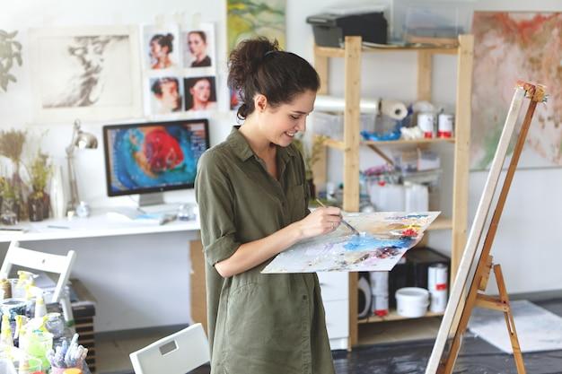 Indoor portret van gelukkig opgewonden jonge vrouw kunstenaar in shirt van militaire kleur met palet en penseel tijdens het werken aan schilderen in haar atelier, staande voor ezel en glimlachen