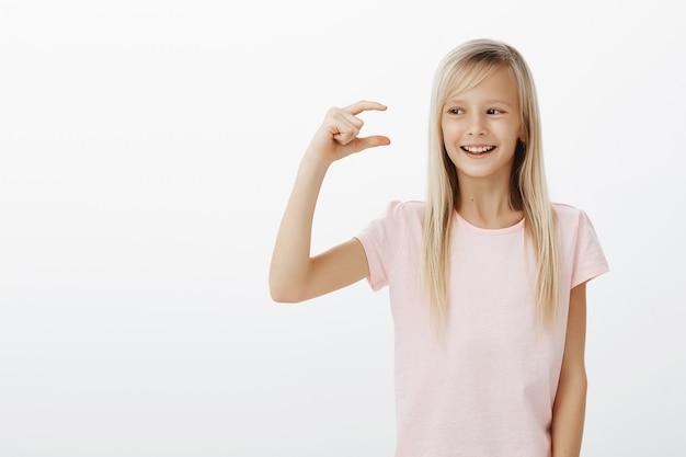Indoor portret van gelukkig tevreden schattig jong meisje met blond haar, kijken naar klein ding, vormgeven met vingers