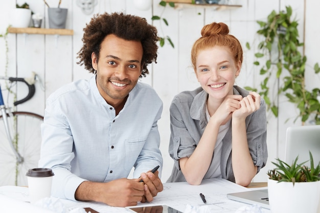 Indoor portret van gelukkig verenigd multi-etnisch team van twee creatieve werkers